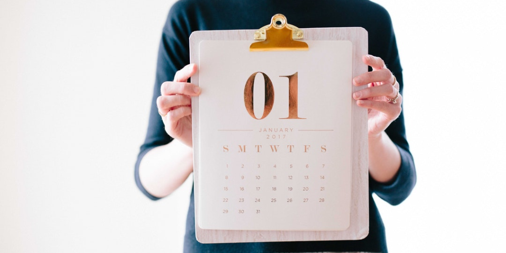 woman holding up january calendar month on clipboard