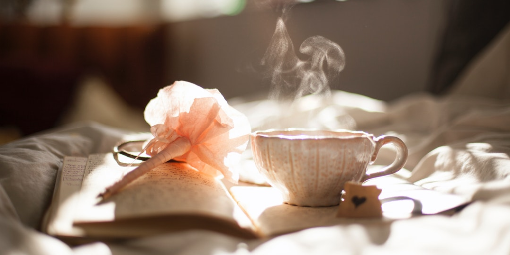 steaming teacup sitting on top of journal on bed