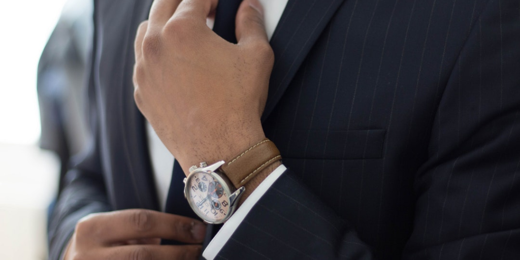 man with watch adjusting tie on suit