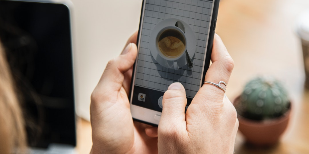 woman taking picture of coffee on phone