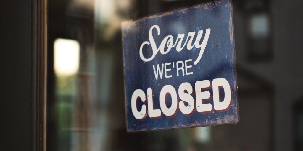 wooden sign hanging inside glass window that says sorry we're closed