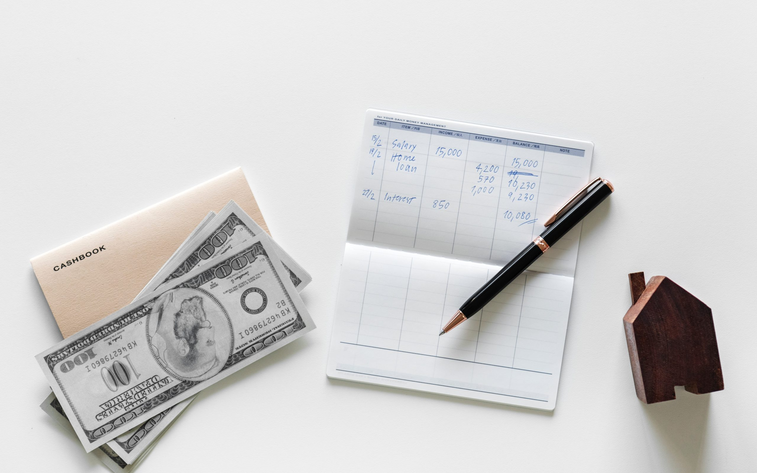 cashbook, money, and pen sitting on table
