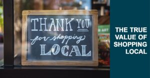 "chalkboard behind window that reads ""thank you for shopping local"""