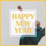 """Golden text """"Happy New Year"""" rests on top of image of woman in green jacket throwing confetti."""