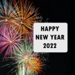 """Black """"Happy New Year 2022"""" text on a white square background. White background is on right side of an image of orange, green, and purple fireworks in a dark night time sky."""