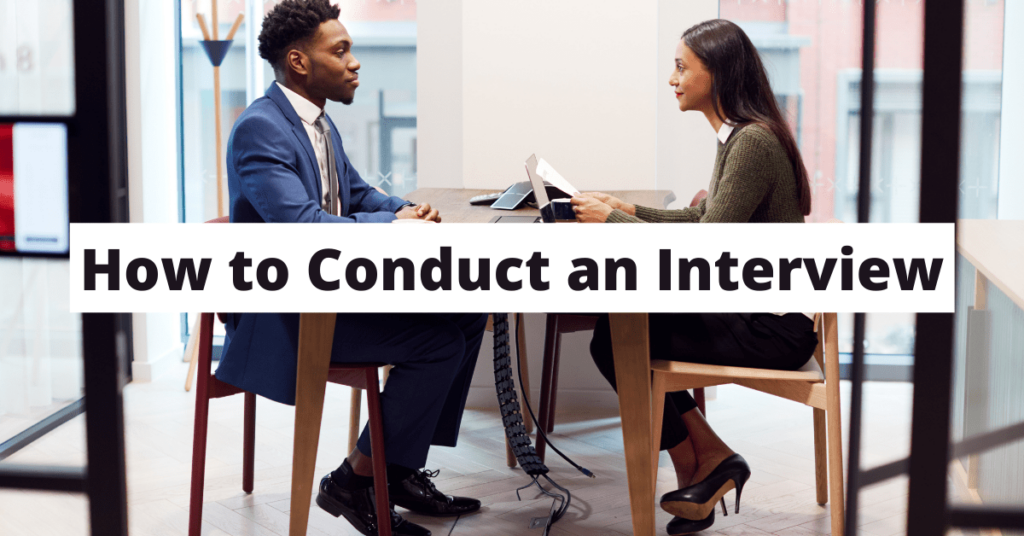 Image of man and woman at table in professional clothes having an interview. Black text on white backgroud says